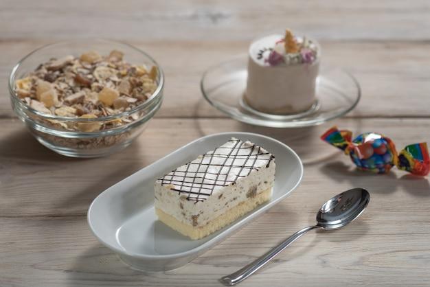 나무 배경에 조류의 우유 접시에 halva, 초콜릿, muesli와 케이크.