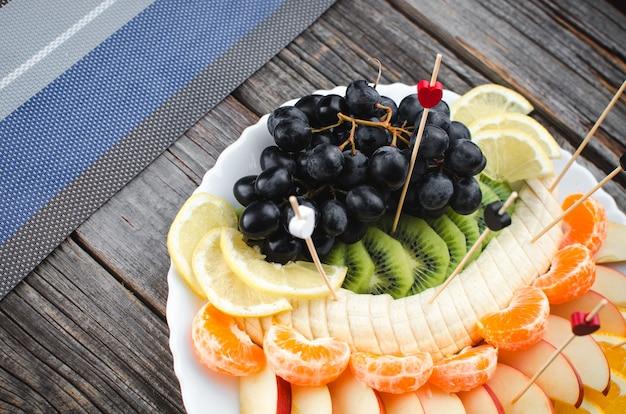 하얀 접시에 있는 나무 배경에 과일 슬라이스, 아름답게 배치