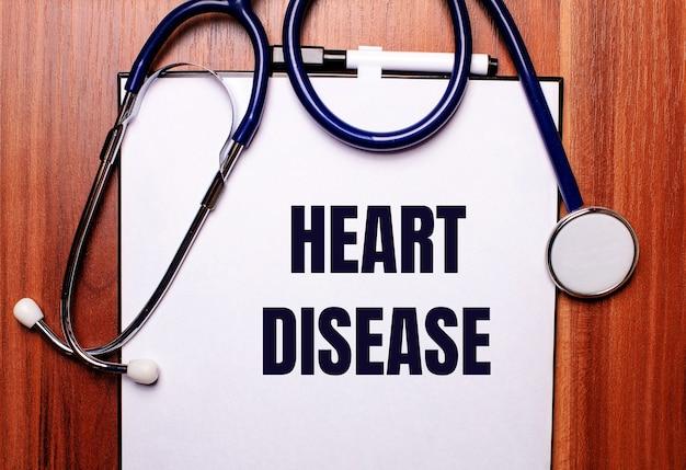 나무 배경에는 청진기와 심장병이 새겨진 종이가 놓여 있습니다. 플랫 레이. 의료 개념