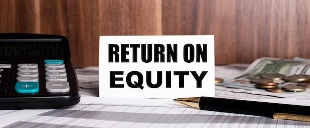 木製の背景に電卓と単語の白いカードが付いているペンがありますreturnon equity