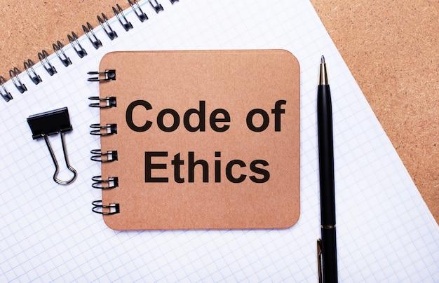 木製の背景のメモ帳、黒いペン、ペーパークリップ、茶色のメモ帳にcde ofethicsというテキストが表示されます。ビジネスコンセプト