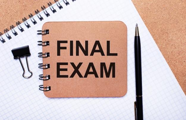 木製の背景のメモ帳、黒いペン、ペーパークリップ、茶色のメモ帳に「finalexam」というテキストが表示されます。ビジネスコンセプト