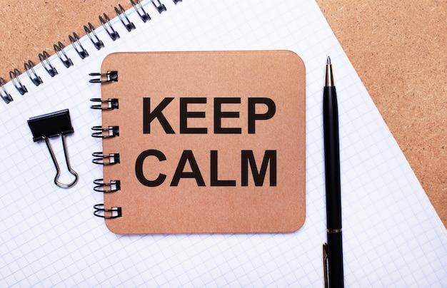 На деревянном фоне блокнот, черная ручка, скрепка и коричневый блокнот с надписью keep calm. бизнес-концепция