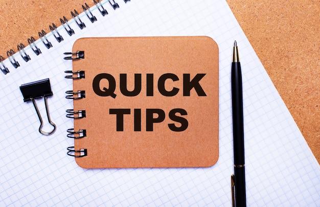 木製の背景のメモ帳、黒いペン、ペーパークリップ、茶色のメモ帳にquicktipsというテキストが表示されます。ビジネスコンセプト