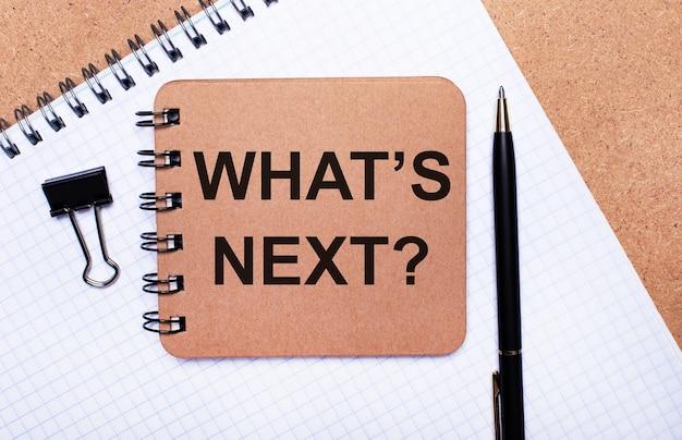 木製の背景のメモ帳、黒いペン、ペーパークリップ、茶色のメモ帳に、「次は何ですか」というテキストが表示されます。ビジネスコンセプト