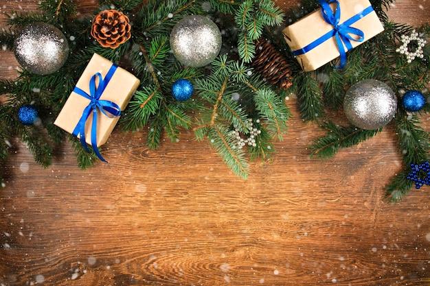 青いリボンの円錐形とトウヒの枝と青い贈り物の木製の背景飾りに