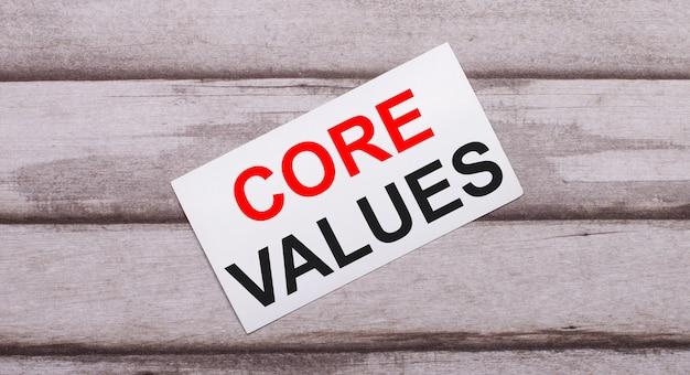 На деревянном фоне есть белая карточка с красным текстом основные ценности. Premium Фотографии