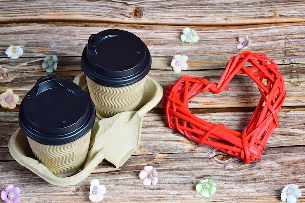 나무 배경에 오른쪽에 두 잔의 커피가 있고 오른쪽에 큰 장식 고리버들 하트가 있습니다. 작은 꽃들이 주위에 흩어져있다.