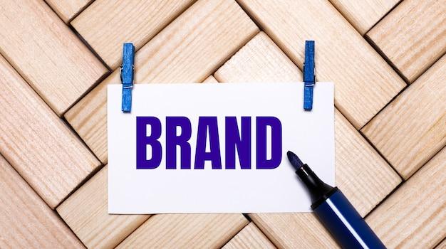 На деревянной поверхности белая карточка с надписью бренд на синих прищепках и синим маркером.