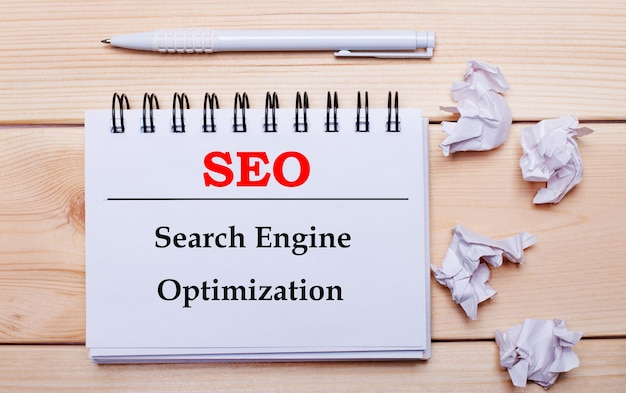 На деревянной поверхности белый блокнот с надписью seo search engine optimization, белая ручка и скомканные белые листы бумаги.