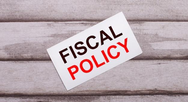 На деревянной поверхности есть белая карточка с красным текстом fiscal policy.