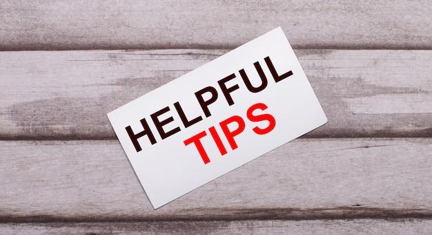나무 표면에 빨간색 텍스트가있는 흰색 카드가 있습니다 helpful tips