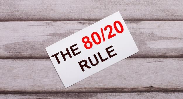 나무 표면에는 빨간색 텍스트 the 80 20 rule이있는 흰색 카드가 있습니다.