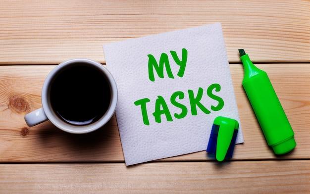 나무 테이블, 커피 한 잔, 녹색 마커, my tasks라는 텍스트가있는 냅킨.