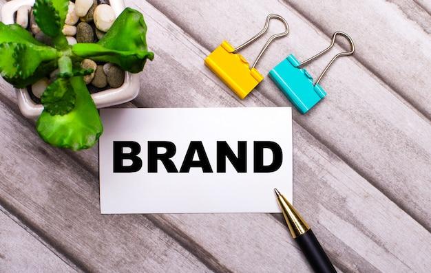 На деревянном столе белая карточка с текстом бренд, желтые и зеленые скрепки и растение в горшке. вид сверху