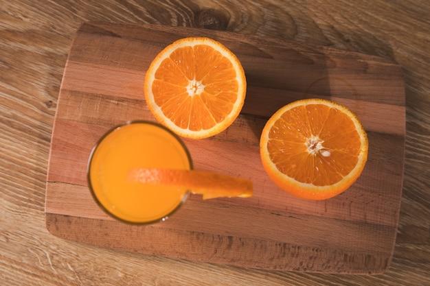 나무 테이블에 오렌지와 음료와 함께 유리