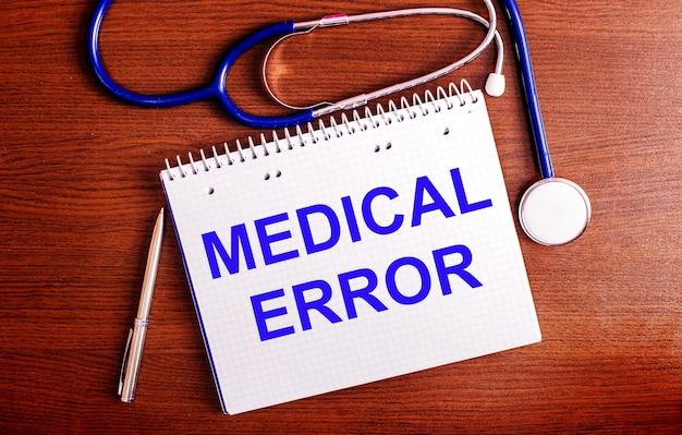 木製のテーブルには、ペン、聴診器、およびmedicalerrorというラベルの付いたノートがあります。医療の概念