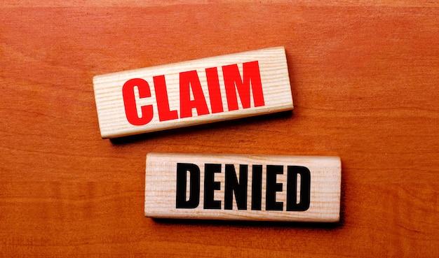 На деревянном столе два деревянных блока с текстом «претензия отказана».