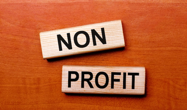 木製のテーブルには、「nonprofit」というテキストの質問が書かれた2つの木製のブロックがあります。