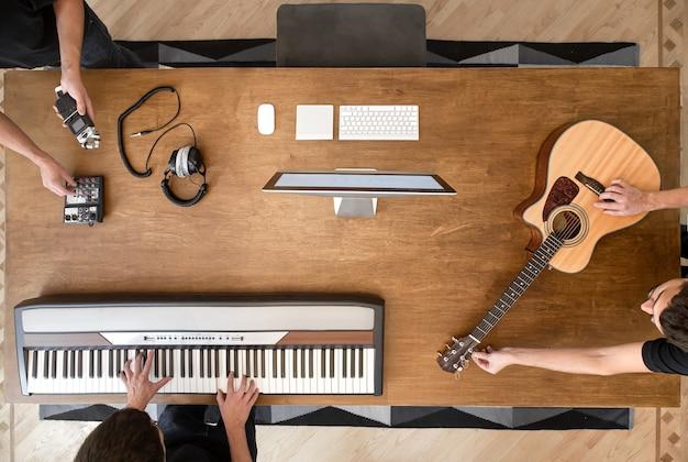 녹음 스튜디오의 나무 테이블, 음악 키보드, 어쿠스틱 기타, 사운드 믹서 및 컴퓨터.