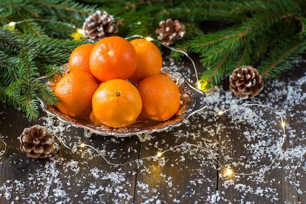 На деревянном столе в серебряной тарелке мандарины, а вокруг еловые ветки, шишки
