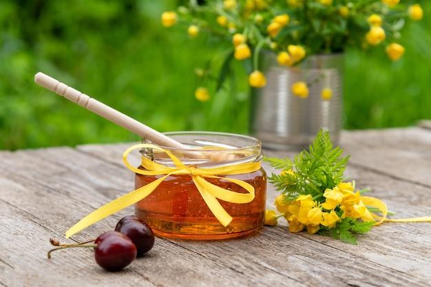 На деревянном столе стоит стеклянная банка с медом.