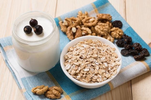 На деревянном столе мюсли, орехи и йогурт в банке, концепция здорового питания