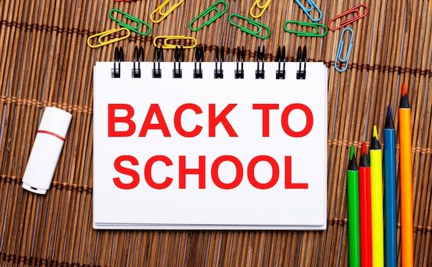 木製のテーブルの上に、色鉛筆、ペーパークリップ、白いフラッシュドライブ、「学校に戻る」というテキストが書かれたノートがあります。フラットレイ