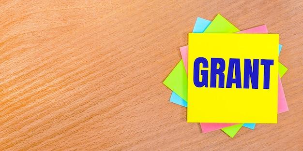 На деревянном столе разноцветные наклейки с надписью grant. копировать пространство
