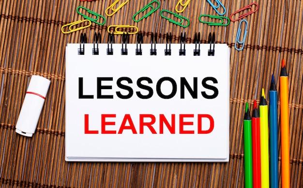 나무 테이블, 다색 연필, 종이 클립, 흰색 플래시 드라이브 및 lessons learned 텍스트가있는 노트북