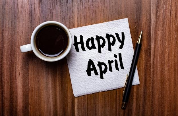 흰색 컵 커피와 펜 옆에있는 나무 테이블에는 happy april이라는 단어가 적힌 흰색 종이 냅킨이 있습니다.