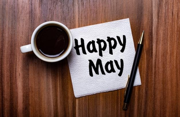 На деревянном столе рядом с белой чашкой кофе и ручкой лежит белая бумажная салфетка с надписью happy may.