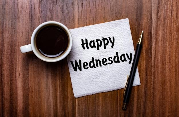 На деревянном столе рядом с белой чашкой кофе и ручкой лежит белая бумажная салфетка с надписью happy wednesday.
