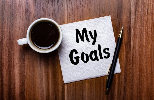 흰색 컵 커피와 펜 옆 나무 테이블에는 my goals라는 단어가 적힌 흰색 종이 냅킨이 있습니다.