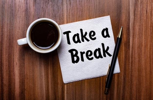 白い一杯のコーヒーとペンの横にある木製のテーブルには、take abreakという言葉が書かれた白い紙ナプキンがあります。