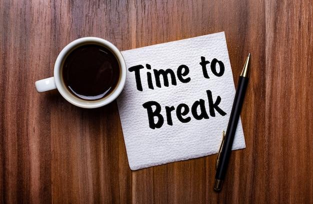白い一杯のコーヒーとペンの横にある木製のテーブルには、「休憩する時間」という言葉が書かれた白い紙ナプキンがあります。