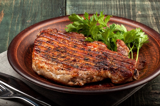 На деревянном столе на белом блюде лежит кусок жареной свинины с зеленью, вид крупным планом