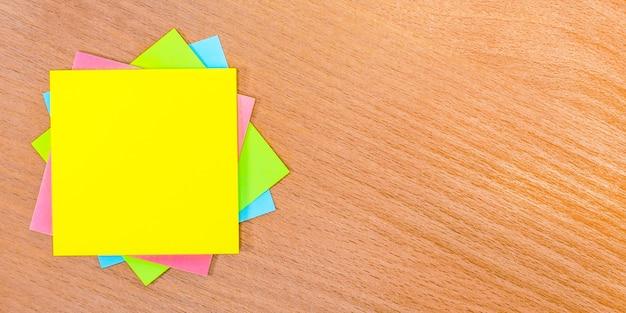 木製のテーブルには、テキストを挿入する場所が付いた色とりどりのステッカーがあります。テンプレート。コピースペース