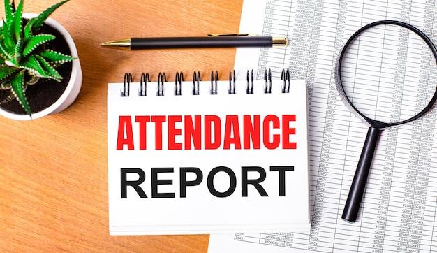 木製のテーブルには、レポート、鉢植え、虫眼鏡、黒いペン、「出席レポート」というテキストが書かれたノートがあります。ビジネスコンセプト