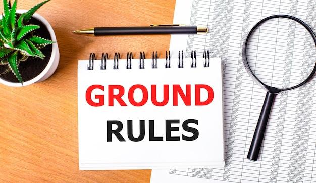 На деревянном столе отчеты, растение в горшке, увеличительное стекло, черная ручка и блокнот с текстом правила назначения. бизнес-концепция
