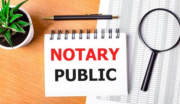 На деревянном столе отчеты, растение в горшке, лупа, черная ручка и блокнот с текстом «нотариус». бизнес-концепция