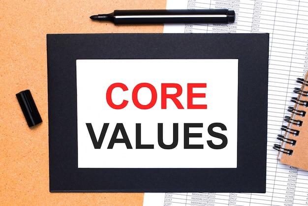 На деревянном столе есть черный открытый маркер, коричневый блокнот и лист бумаги в черной рамке с текстом основные ценности. вид сверху.