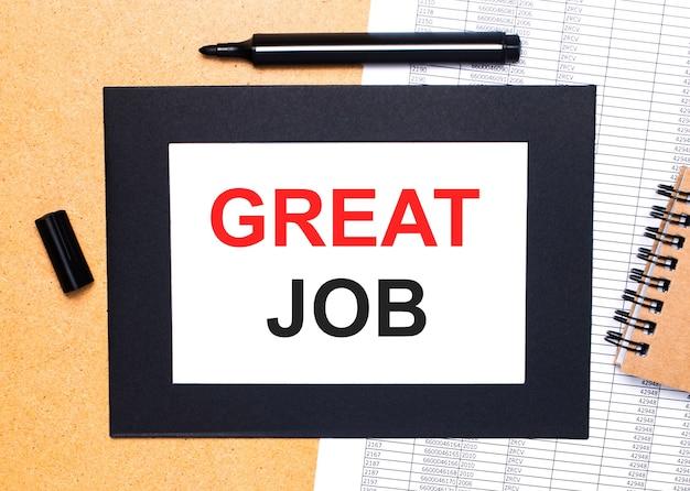 На деревянном столе есть черный открытый маркер, коричневый блокнот и лист бумаги в черной рамке с надписью great job. вид сверху.