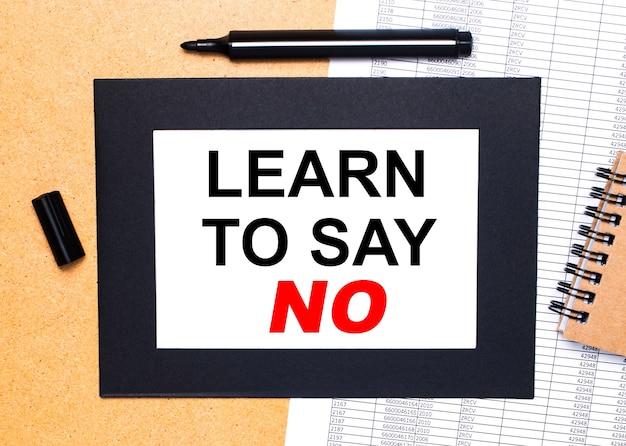 나무 테이블 위에는 검은 색 열린 마커, 갈색 메모장, 검은 색 프레임에 'learn to say no'라는 텍스트가있는 종이가 있습니다. 위에서 봅니다.