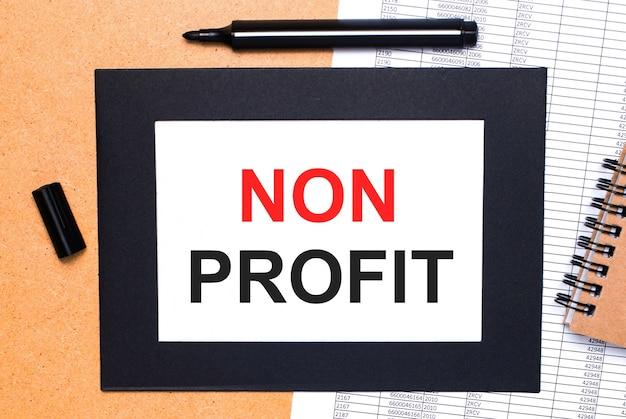На деревянном столе черный открытый маркер, коричневый блокнот и лист бумаги в черной рамке с надписью non profit. вид сверху.