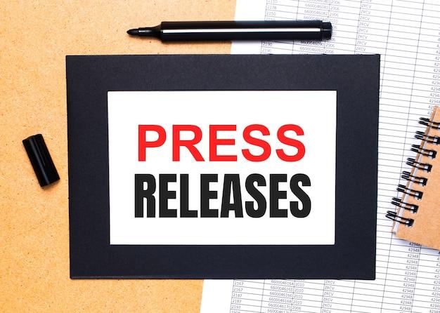 На деревянном столе черный открытый маркер, коричневый блокнот и лист бумаги в черной рамке с текстом пресс-релизы. вид сверху.
