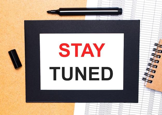 На деревянном столе есть черный открытый маркер, коричневый блокнот и лист бумаги в черной рамке с надписью stay tuned. вид сверху.