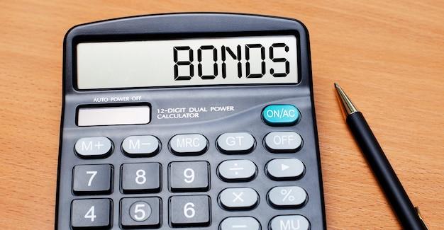 На деревянном столе есть черная ручка и калькулятор с текстом bonds. бизнес-концепция