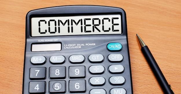 На деревянном столе есть черная ручка и калькулятор с надписью commerce. бизнес-концепция