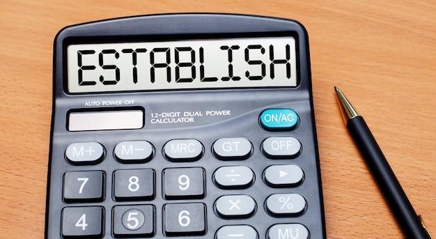 На деревянном столе есть черная ручка и калькулятор с текстом установить. бизнес-концепция